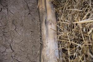 A gauche le torchis (terre du jardin, mélangé à de la paille), au centre le poteau en bois de châtaignier coupé main, et à droite le mur en paille encore brut © Eric Raz/ccas