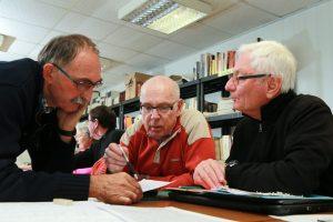 Claude, Jean-Claude et Bertrand s'entraident déchiffrer un document d'état civil rédigé en vieux Français © Charles Crié/CCAS