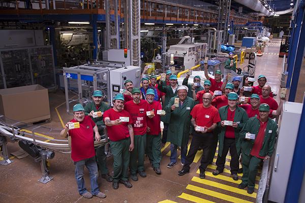 Au milieu de l'allée principale de la chaîne de production, une partie de l'équipe SCOP-TI pose pour la CCAS©E.Raz/ccas