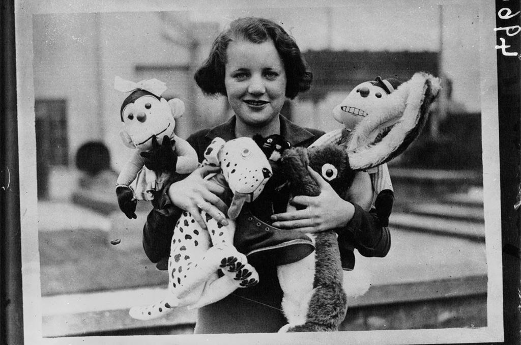 Jeune fille tenant des jouets pour la Noël. ©BNF [photographie de presse]/Planet