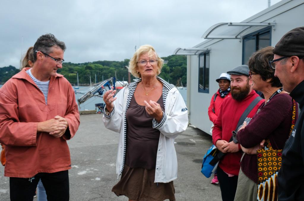 """Diane Levesque et Bruno Rathouit, président de la CMCAS, (à g.) accueillent les navigateur·rices du """"Kendalc'h""""."""