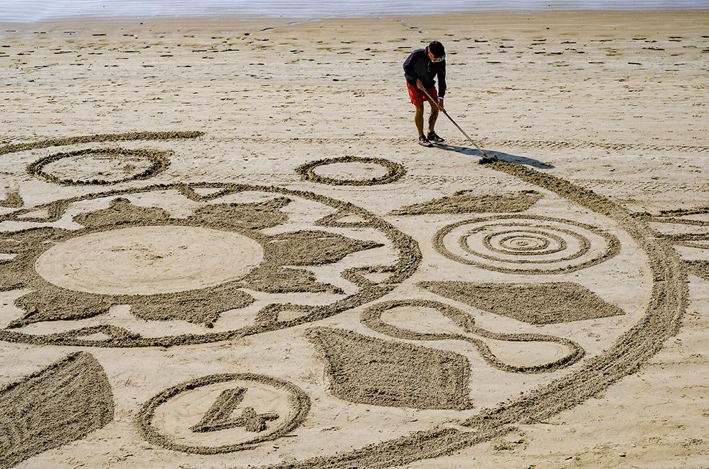 personnage dessinant sur le sable sur une plage des sables d'olonne ccas