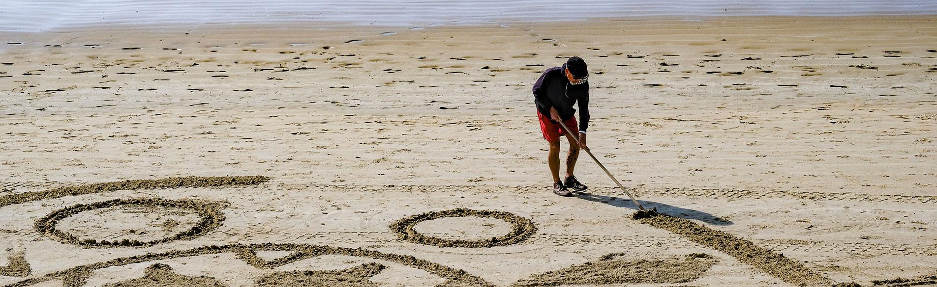 personne dessinant sur une plage des sables d'olonne